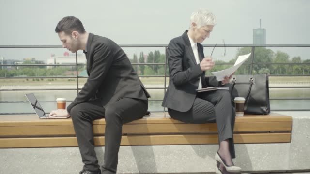 Business People sitting on bench and looking at papers.