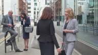 Business people talking in the street in London