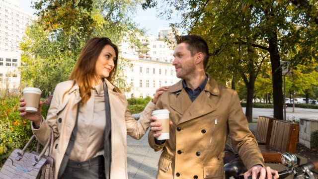 Business people walking outdoors with coffee