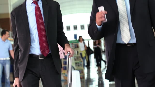 Business people walking through airport terminal / discussion