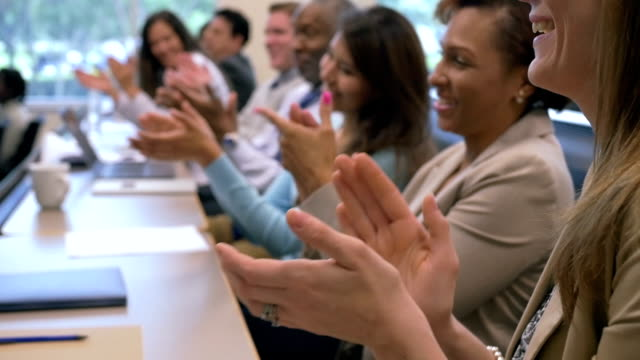Business professionals applauding speaker at conference or seminar