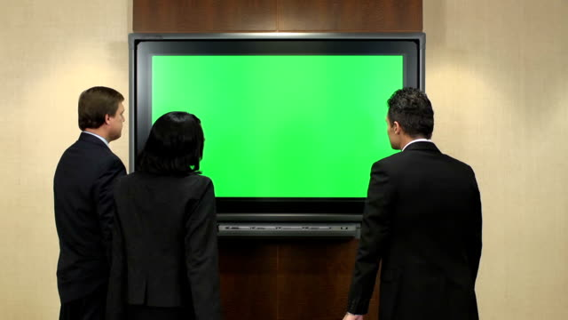 Business Professionals in Front of Chroma Key Monitor