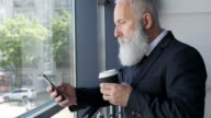Business. Senior businessman reading a message on a smartphone