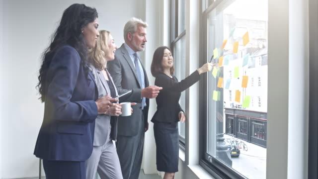 Business-Team besprechen Ideen auf Notizen im Büro schreiben