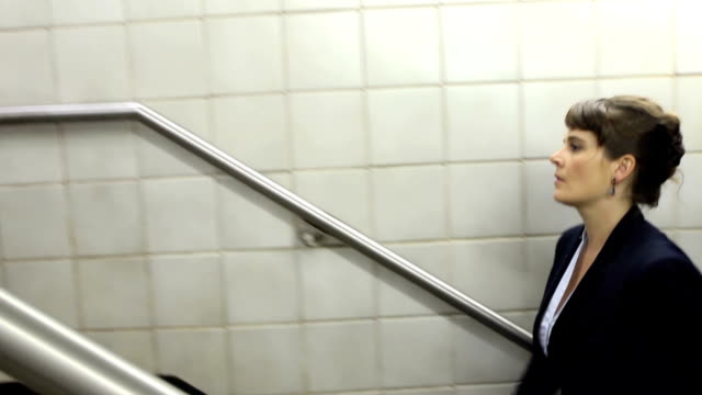 Business Woman Climbs Stairs in Subway Station