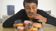 business woman eating a pile of donuts
