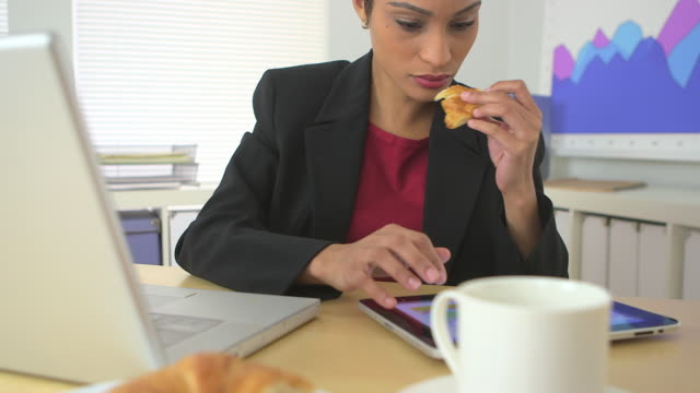 business woman eating croissant and using tablet computer