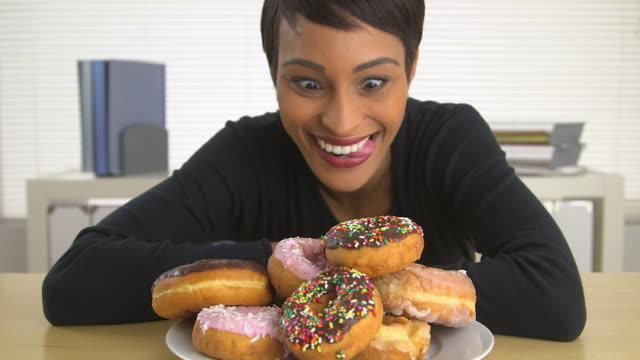 business woman looking at pile of donuts
