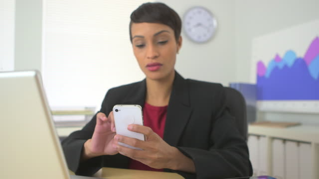 business woman picking up cell phone while working