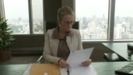 MS PAN Business woman reading documents in office / Bangkok, Thailand