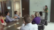 MS ZI Business woman receiving applause, talking to colleagues in conference room / Bangkok, Thailand