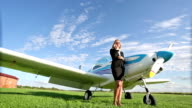 Business woman standing next to a small airplane