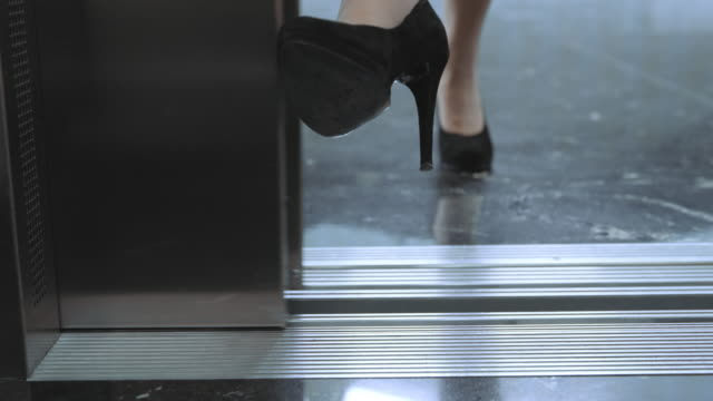 DS Business woman stops the elevator door with her foot and enters