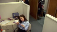 MS, HA,  Business woman talking on phone, colleague stopping by cubicle for chat, Compton, California, USA