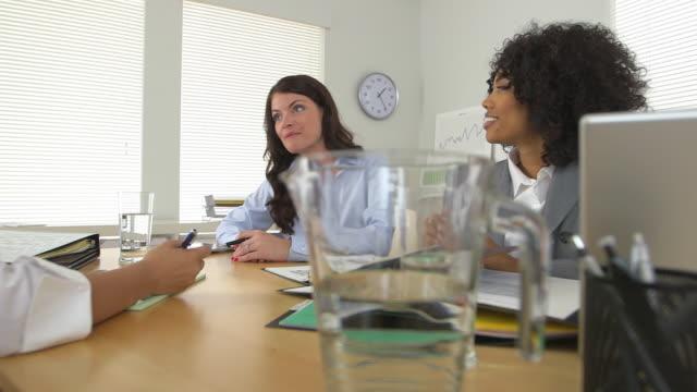 business woman talking to co workers across desk