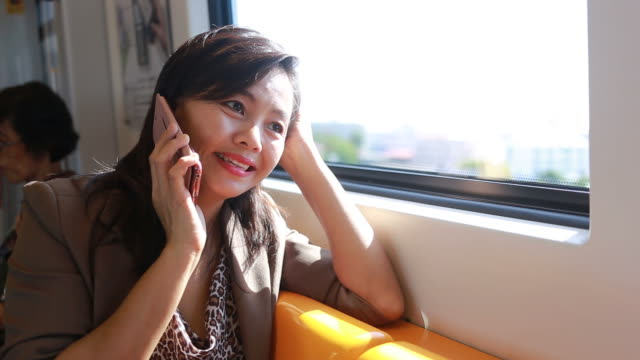 business woman using smartphone on city train
