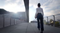 Business woman walks over pedestrian bridge