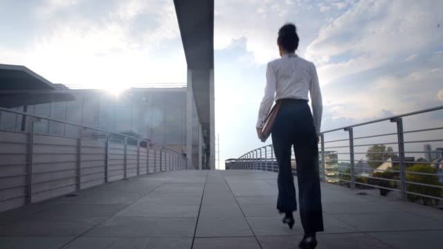 Business woman walks over pedestrian bridge