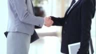 SLO MO LD Business women shaking hands in hallway
