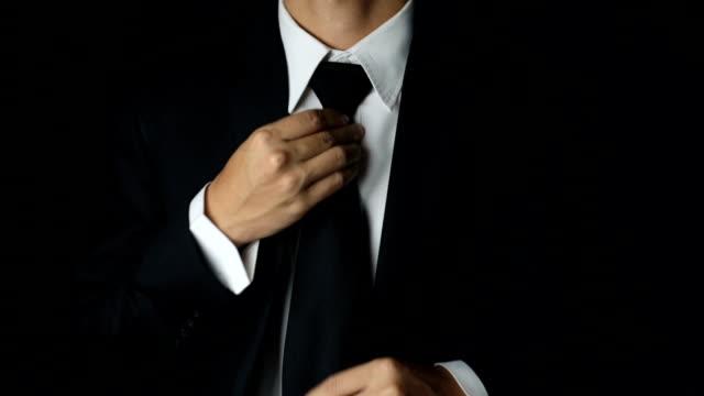 Affärsman justera halsduk hans kostym