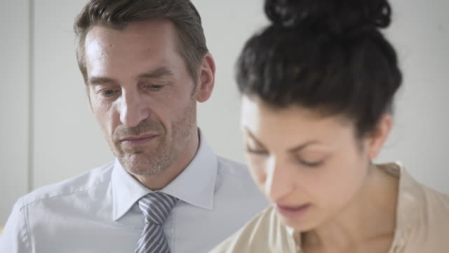 Businessman and business woman talk over a break in a creative, stylish office kitchen