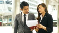 DS MS Businessman and businesswoman discussing paperwork
