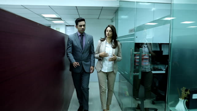 Businessman and businesswoman entering in the office, Delhi, India