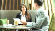 Businessman and businesswoman have small meeting about there business performance in coffee shop.