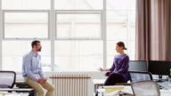 MS businessman and businesswoman in discussion at workstations in office