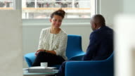 MS Businessman and businesswoman in discussion during informal meeting in office