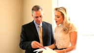 Businessman and Businesswoman Look Over Documents.