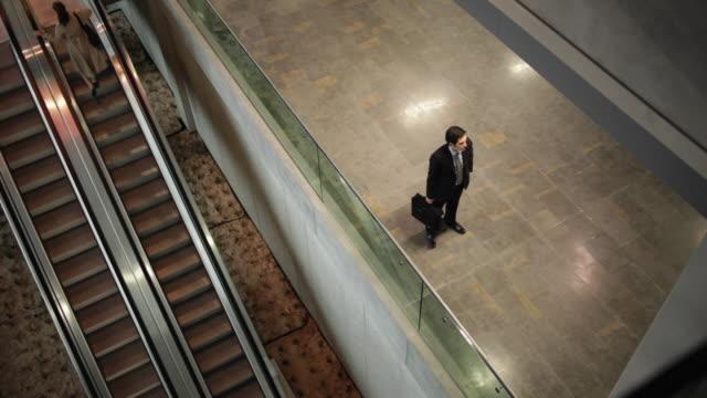 WS HA Businessman and businesswoman meeting in airport terminal near escalators / Toulouse, Haute-Garonne, France