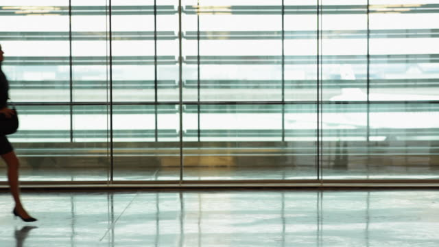 WS Businessman and businesswoman running in airport terminal / Toulouse, Haute-Garonne, France