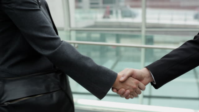 CU Businessman and businesswoman shaking hands on airport bridge, close-up of hands / Toulouse, Haute-Garonne, France