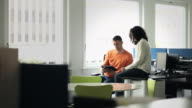 MS businessman and businesswoman sitting at workstation in office working on digital tablet