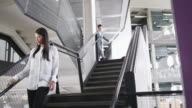 Businessman and businesswoman walking down stairs in an office