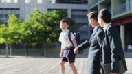 MS of businessman and businesswoman walking outdoors with their son, selective focus