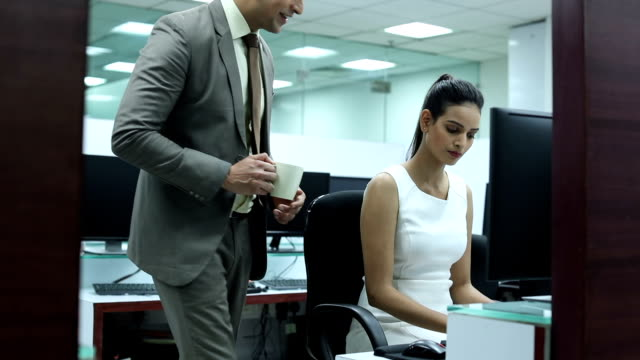 Businessman and businesswoman working on computer in the office, Delhi, India