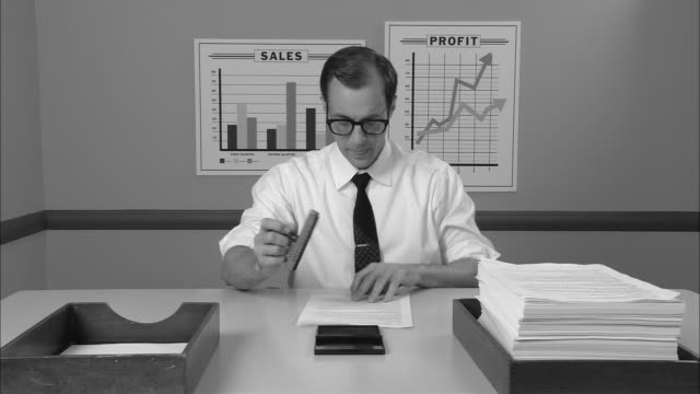 B/W MS Businessman at desk rolling up sleeves and beginning to stamp stack of papers  moving them from inbox to outbox/ New York City