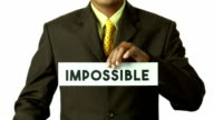 Businessman cut the paper for turning word 'IMPOSSIBLE' into 'POSSIBLE'