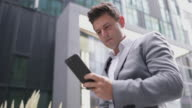 Businessman cycling to a meeting using smartphone