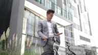 Businessman cycling to work using smartphone