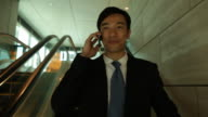 A businessman descends on an escalator as he talks on a cellphone.