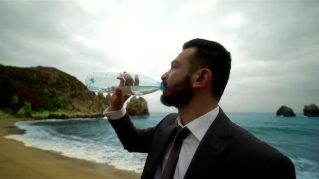 Businessman Drinking Water on the Beach - 4K Resolution