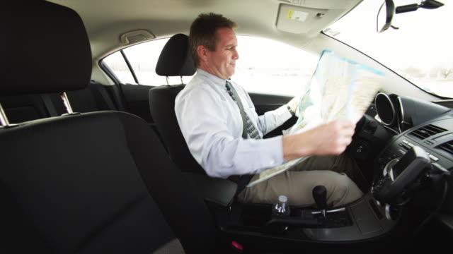 MS Businessman driving car and reading map / Orem, Utah, USA