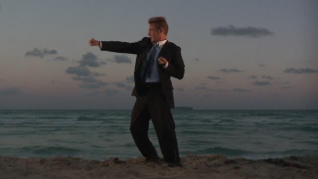 WS SLO MO Businessman exercising on beach / South Beach, Florida, USA