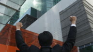 A businessman faces office buildings and raises his fists in the air.