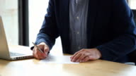 MS Businessman filling out paperwork during meeting at office conference room table
