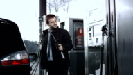 HD DOLLY: Businessman Filling Up A Gas Tank