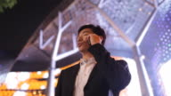 A businessman gazes around at the city lights as he talks on a cell phone.